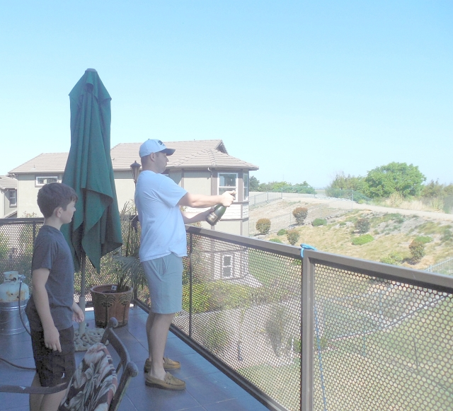 2015-5-24ab Aidan watches Brett pop the cork for Sunday mimosas.