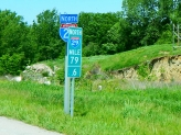 Why do some states place a mile marker every tenth mile, and also a larger sign after each onramp? It seems a foolish waste of money and this photo proves it.