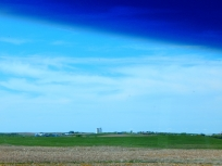 Looking out across the landscape to a large farm complex.