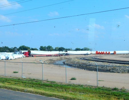 There is a large wind turbine facility in Garden City, KS. To the right of the photo are sections of the tower, in the center are single blades loaded on over sized big rigs, and to the left are the nose cones. This should add clarity to one's understanding of the size of a wind turbine.