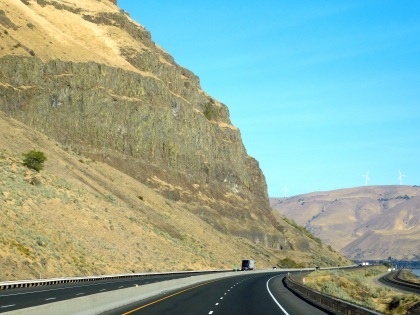 Towering cliffs dwarf the traffic along I-84 along the Columbia River.