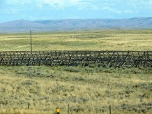 A Wyoming snow fence that causes blowing snow to drop and not cover the highway. I am pleased to report that when we drove through, the fences were working as designed; we didn't see a single snow flake all day!