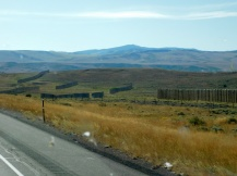 A better photo of snow fences which are built all along I-80 in Wyoming. As is clearly shown, they really do work - there's not a snow flake to be seen for miles!